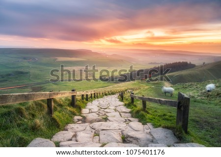 Morning sun casting golden light on the landscape at Mam Tor in the English Peak District. Royalty-Free Stock Photo #1075401176