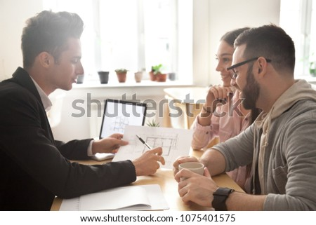 Interior designer discussing apartment renovation idea with happy couple at meeting, smiling customers consider mortgage investment loan or flat purchase consulting realtor showing architectural plan Royalty-Free Stock Photo #1075401575