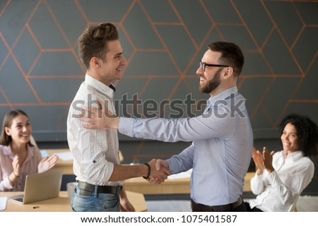 Team leader handshaking employee congratulating with professional achievement or career promotion, thanking for good project result while team supporting applauding, appreciation recognition concept #1075401587