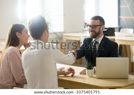 Smiling lawyer, realtor or financial advisor handshaking young couple thanking for advice, insurance broker or bank worker and millennial customers shake hands making deal, investment or taking loan Royalty-Free Stock Photo #1075401791
