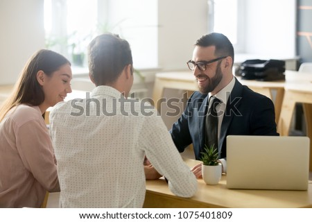 Friendly lawyer or financial advisor in suit consulting young couple, smiling investment broker or bank worker making loan offer, giving legal advice, selling insurance or real estate to customers Royalty-Free Stock Photo #1075401809