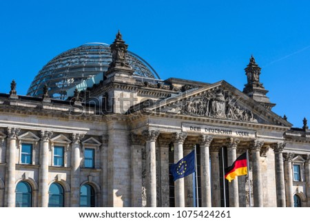 Germany, Berlin: National and European flag and famous part of parliament building Deutscher Bundestag (former Reichstag) in the city center of the German capital with blue sky. #1075424261
