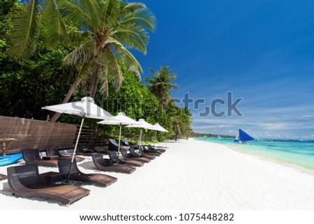 Sun umbrellas and beach chairs on tropical coastline, Philippines, Boracay #1075448282
