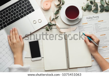 Wedding arrangement background. Female hands preparing for marriage, using laptop, smartphone, paper calendars and planners, top view. Bridal wallpaper with copy space on to do list #1075451063