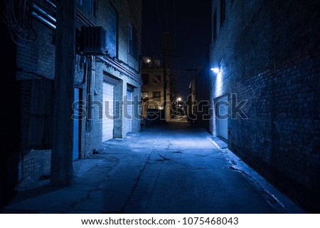 Dark and eerie urban city alley at night Royalty-Free Stock Photo #1075468043