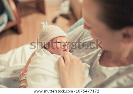 Mother holding her new born baby boy.  Royalty-Free Stock Photo #1075477172