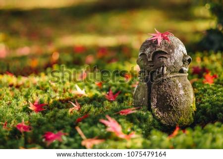 Red Maple leaf on head of Jizo  sculpture doll (little Japanese Buddhist monk doll rock) in Japanese Garden, Enkoji Temple, Kyoto, Japan. Autumn season japan #1075479164