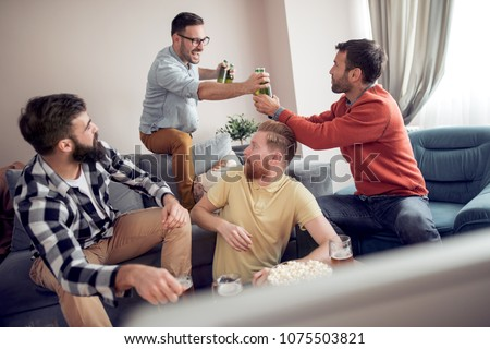 People, men, leisure, friendship and technology concept-happy male friends drinking beer and having fun at home. #1075503821