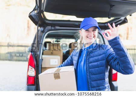 Smiling female postal delivery courier woman outdoors in front of cargo van delivering package #1075568216