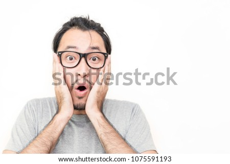 Portrait of young asian man in shock isolated on white. Crazy desperate man shocked looking at camera with wide opened mouth. Anxious male trembling horror fear. Negative emotions feelings concept #1075591193