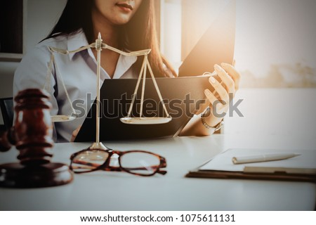 Business woman and lawyers discussing contract papers with brass scale on wooden desk in office. Law, legal services, advice, Justice and real estate concept. #1075611131