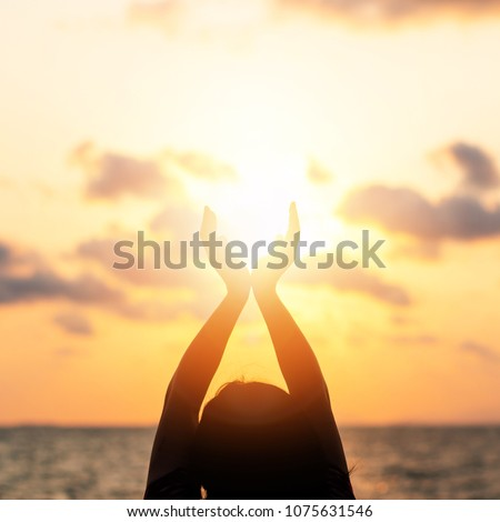 June summer sun solstice concept with silhouette of happy young woman's hands relaxing, meditating and holding sunset against warm golden hour sky on the beach with natural ocean or sea background #1075631546