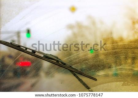 Windshield wipers from inside of car, season rain. Royalty-Free Stock Photo #1075778147