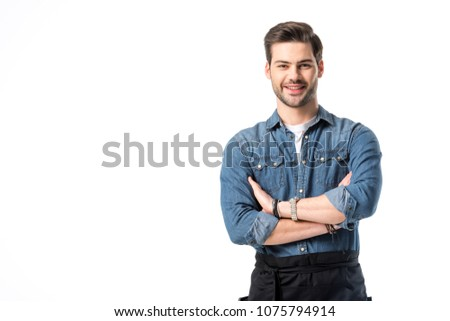portrait of smiling waiter in apron with arms crossed isolated on white #1075794914