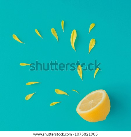 Creative summer layout made of lemon and yellow flower petals on bright blue background. Fruit minimal concept. #1075821905