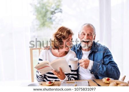 Senior couple eating breakfast at home. #1075831097