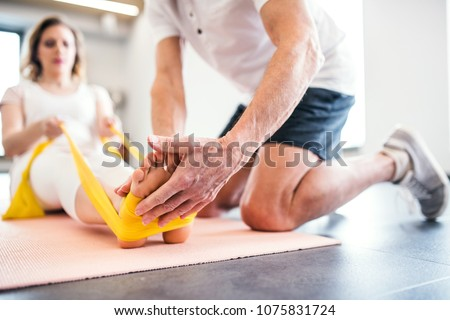 Unrecognizable senior physiotherapist working with a female patient. Royalty-Free Stock Photo #1075831724
