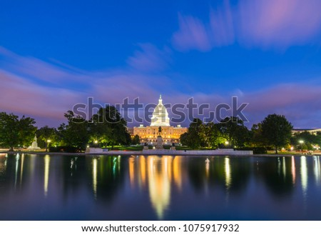 The United States Capitol building at sunset wirh reflection in water.