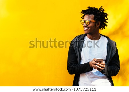 Portrait of handsome afro man using his mobile in the street. Royalty-Free Stock Photo #1075925111