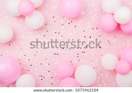 Pastel pink table with frame from balloons and confetti for birthday top view. Flat lay composition. #1075962104