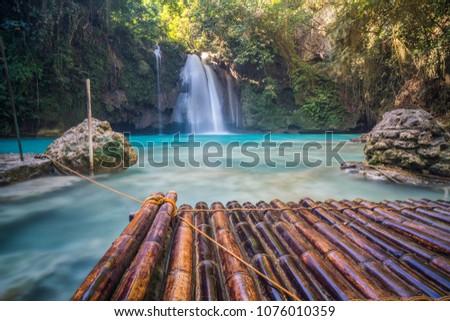 beautiful waterfall and bamboo raft #1076010359