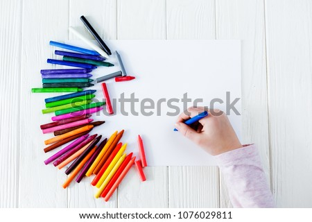 School supplies for drawing on the table: paper and crayons. A child is holding a crayon in his hands #1076029811