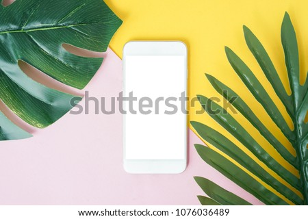 close up on mock up smartphone with blank space in top view perspective with tropical leaves for design concept