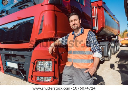 Truck driver in front of his freight forward lorry looking at camera Royalty-Free Stock Photo #1076074724