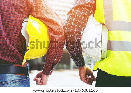 Close up back view of engineering male two construction worker holding safety yellow helmet and white helmet with wear reflective clothing for the safety of the work operation. outdoor of building. #1076081165