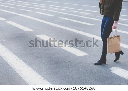 Female Legs Walking On Crosswalk. The Woman Is Wearing Black Shoes On Heels. Shopping Paper Bag In Woman Hand. Space For Text #1076148260