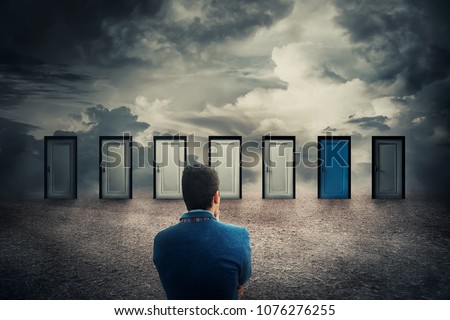 Rear view of a businessman in front of many doors choosing the one different colored. Difficult decision, concept of the important choice in life, failure or success. The ways to unknown future, busin #1076276255