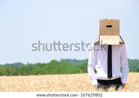 Business man hiding face with box