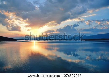 Beautiful Sunset.Sun,lake.Sunrise Landscape.Beauty in Nature.Blue Sky. Amazing Colorful Clouds.Water Reflections.Magic Artistic Wallpaper.Creative Orange Background.Tranquil Natural Art Photography. #1076309042
