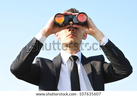 Business man with binoculars on sky