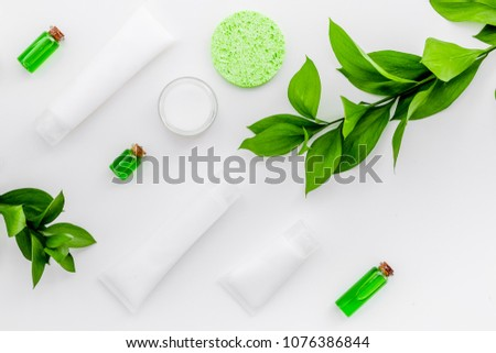 Organic skin care products. Cream, lotion, tonic. oil near green leaves on white background top view pattern #1076386844
