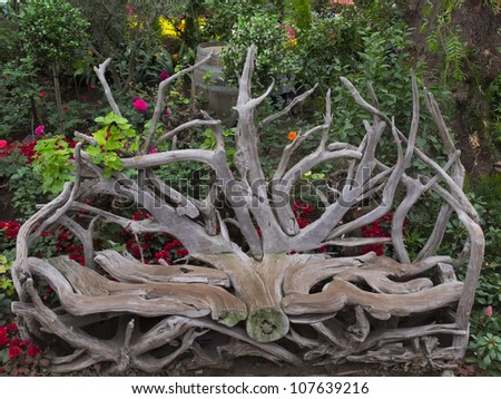 close up of rustic log chair in garden #107639216