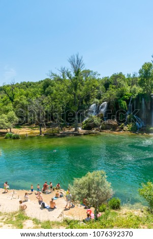 BOSNIA AND HERZEGOVINA, LYUBUSHKI - JUNE 01/2017: tourists rest and swim in the picturesque waterfall. #1076392370