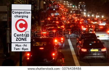 London Congestion Charge Zone Sign over night view of traffic jam, vehicles slow bumper to bumper. #1076438486