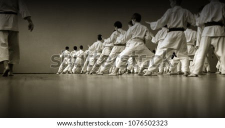 Kids training on karate-do.  Black and white. Photo without faces, from the back. Royalty-Free Stock Photo #1076502323