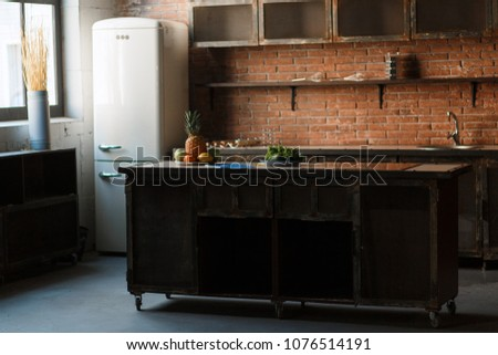 Loft minimalistic kitchen interior photo with retro design fridge and fruits on rustic wooden table. Old fashioned brick wall background