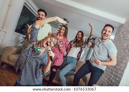 Group of friends playing karaoke at home. Concept about friendship, home entertainment and people #1076533067