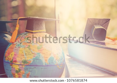 Graduate study abroad program concept : Black graduation cap on a globe map and books, depicts knowledge can be learned online anywhere and everywhere, even in universities or campus around the world. #1076581874