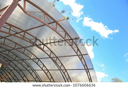 Canopy from polycarbonate arc. Metalware on the blue sky #1076606636