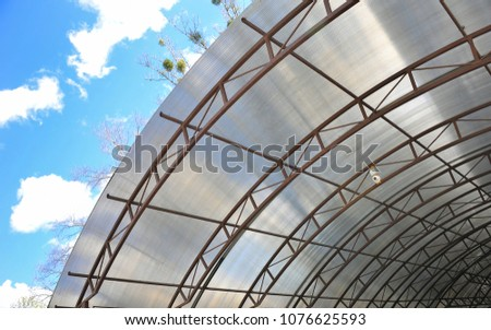 A canopy from polycarbonate arc. Metalware on the blue sky #1076625593