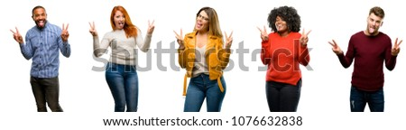 Group of cool people, woman and man looking at camera showing tong and making victory sign with fingers #1076632838