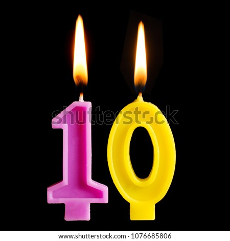Burning birthday candles in the form of 10 ten figures for cake isolated on black background. The concept of celebrating a birthday, anniversary, important date, holiday