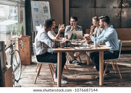 Confident and successful team. Group of young modern people in smart casual wear discussing business while sitting in the creative office Royalty-Free Stock Photo #1076687144