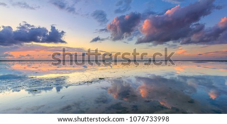 A calm and tranquil zen-like sunset at the beach with beautiful colours in pink and red with reflections on the water - Wadden sea, The Netherlands Royalty-Free Stock Photo #1076733998