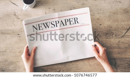 Woman reading newspaper on wooden background Royalty-Free Stock Photo #1076746577