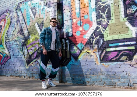 stylish young man in vintage denim jacket and track pants leaning on brick wall with graffiti #1076757176